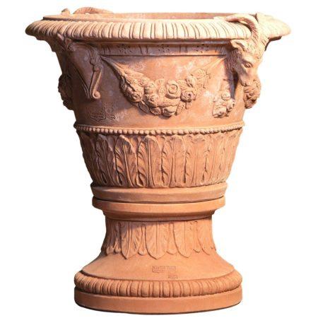 Vaso con stemma e capre e Base con foglie. La forma e il design del vaso lo rendono particolarmente bello ed elegante, aiuta a impreziosire l'arredo e contemporaneamente è adatto per essere piantato. Realizzato a mano da maestri artigiani con argilla di Impruneta, resistente al gelo.