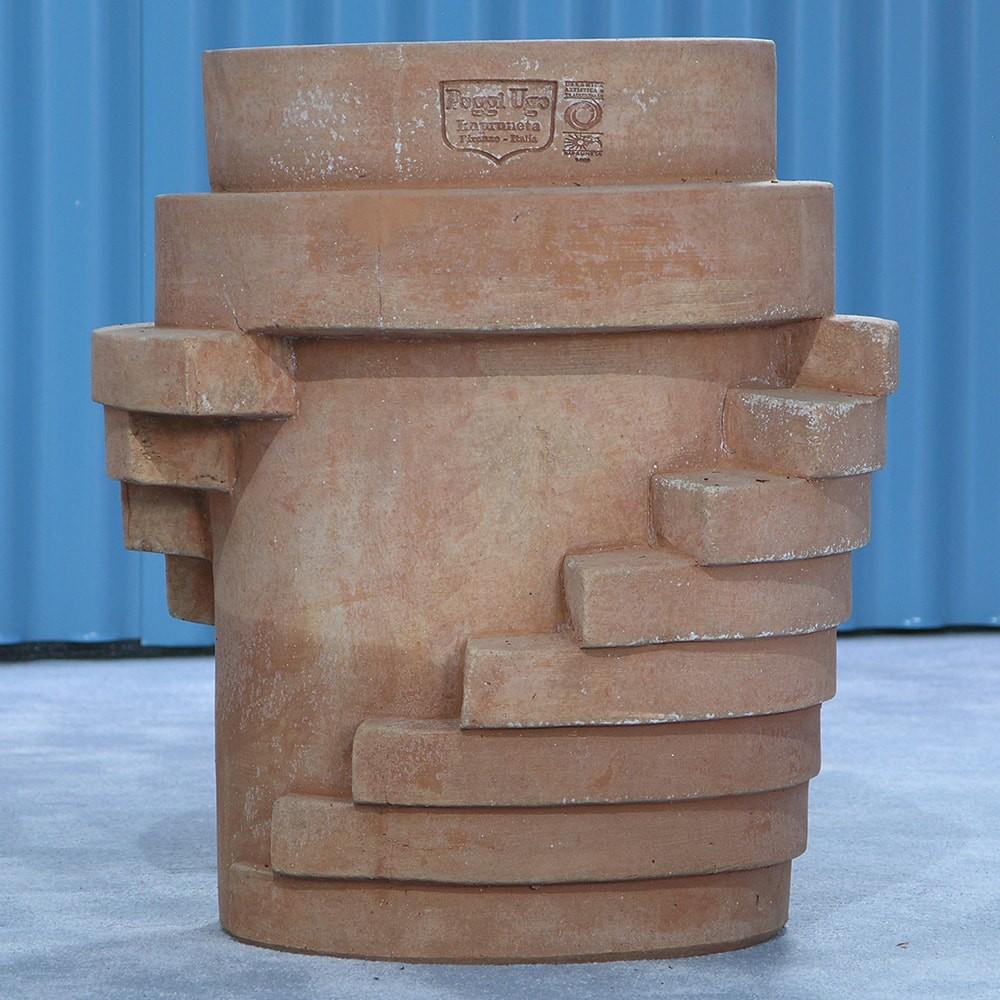 Ana stairs. Disegnato da Ana Milena Hernández Palacios di Masquespacio per i 100 anni delle terrecotte Poggi Ugo, sviluppa una serie di righe a rilievo dalle proporzioni precise, su una scocca di un tipico vaso per le piante. Si ha come l'impressione che il vaso a cono sia protetto come da un robusto guscio dalla forma a gradoni, ripetuti alla stessa distanza uno dall'altro. Alla vista dal dietro partendo da una piccola porzione in alto, si sviluppa a destra e sinistra una sorta di scala che man mano avvolge il vaso primario. Di profilo si ha una visione diversa del vaso tagliato in tralice; di fronte infine, è come se una scala curva scendesse da ambo i lati per avvicinarsi al centro della scena.
