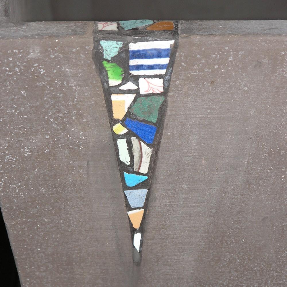 """Vaso quadrato con inserti in ceramica. Vaso per piantare dalla forma troncopiramidale ottimo per svasare le piante, reso unico da inserti di ceramiche colorate con un lavoro manuale e una malta colore grigio. La moderna cassetta presenta un lato liscio e tre lati con lavorazione a mosaico. L'impasto di argilla è detto """"grigiolava"""" per il suo colore metallico. Le ceramiche adoperate sono riconducibili alla tradizione toscana. Pezzo unico non riproducibile in egual disegno."""